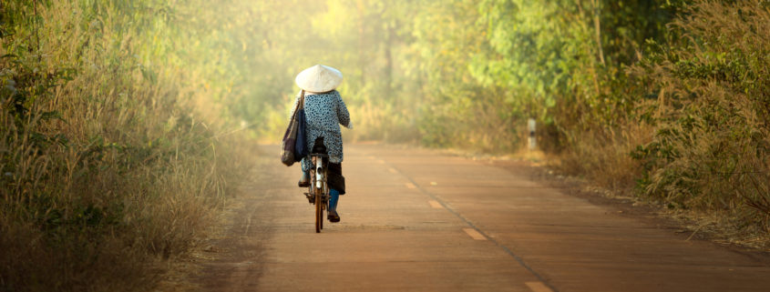 Woman cycling in Cambodia