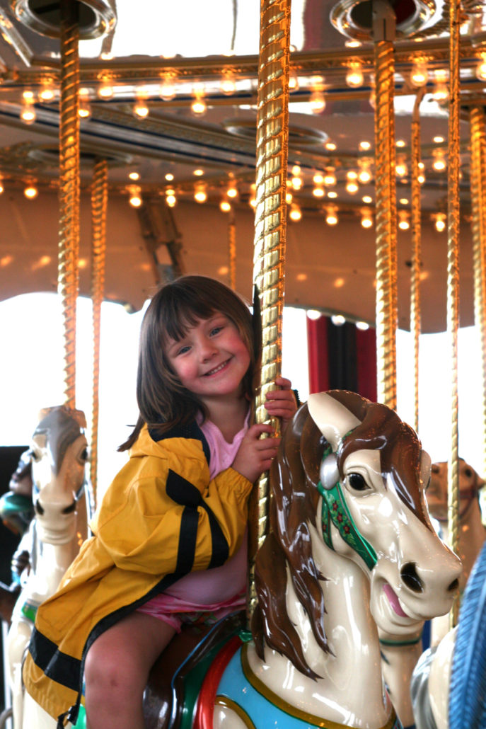Girl riding Carousel in Old Orchard Maine