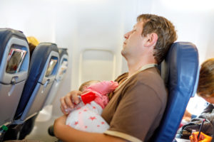 father with baby sleeping on airplane