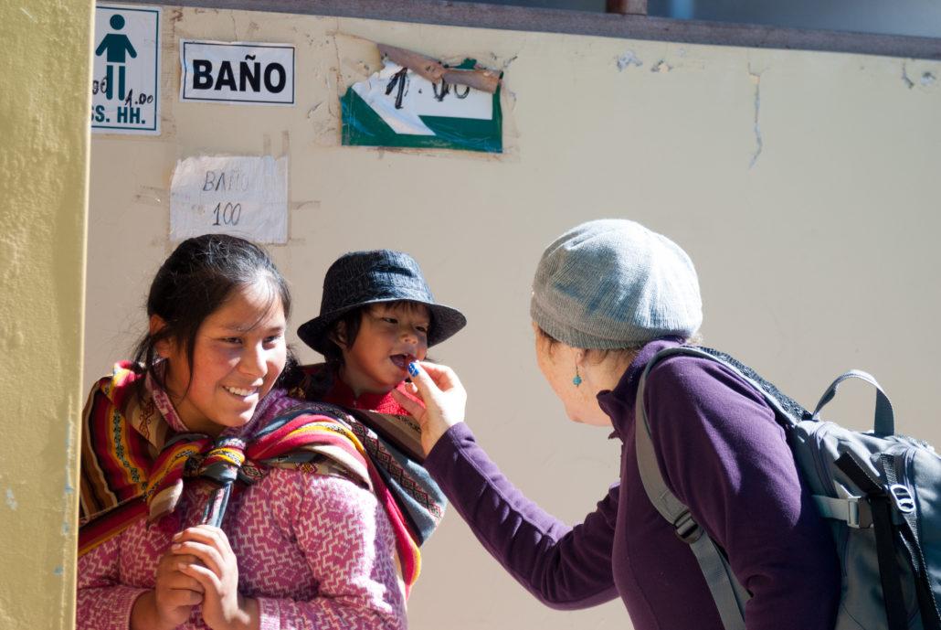 Tourist in Peru feeding child