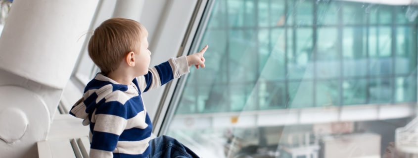 Toddler at Airport looking out the window at planes