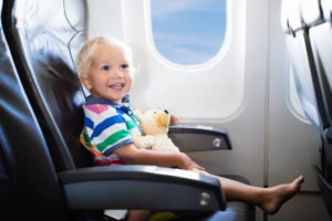 toddler on plane in seat with teddy bear