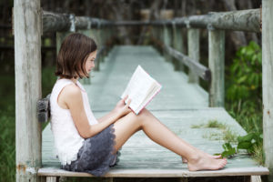 Girl reading on dock by water
