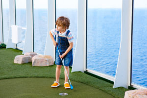 Little boy playing mini golf on a family cruise