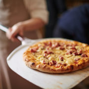 Pizza coming out of oven in Italian restaurant