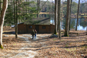 Couple walking to lakeside cabin in the woods