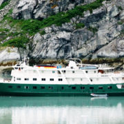 A small green and white cruise boat anchors in glacier bay, Alaska