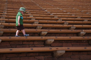 little boy walks along the seats at Red Rocks Amphitheater in Morrison, Colorado.
