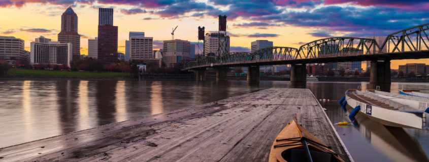 Skyline of Portland Oregon at sunset with kayaks