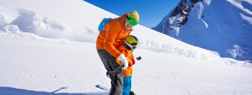 Instructor teaching little boy how to ski skiing with him on piste on mountain resort