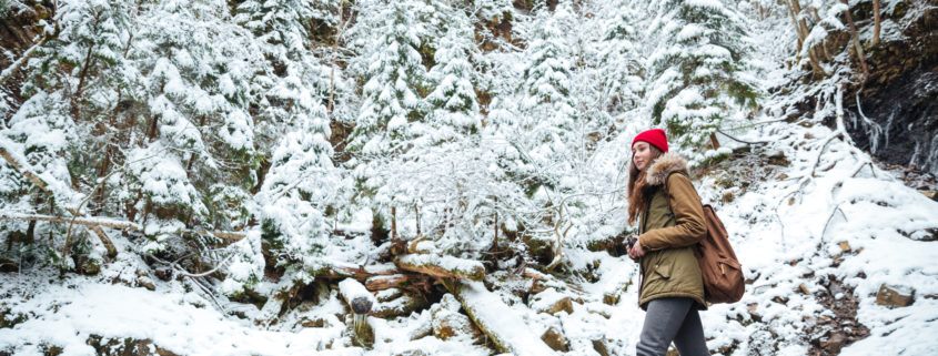 Woman traveling in forest with backpack in winter