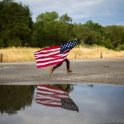 boy running with an American flag