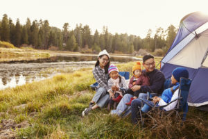 family on a camping trip relax outside their tent