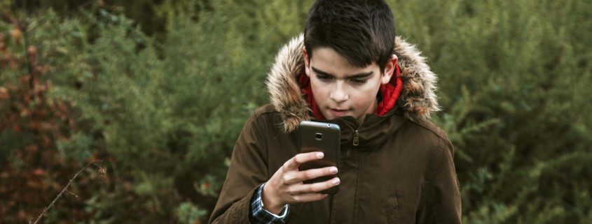 Kid using phone while hiking