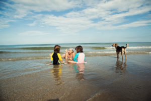 family on beach during vacation with dog