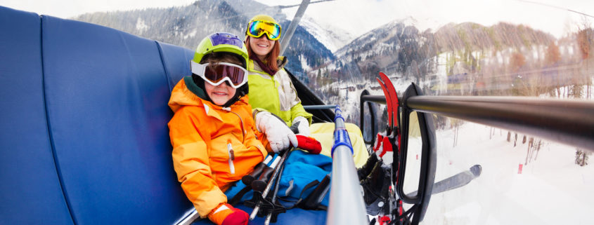 Boy and mother on ski lift in mountains