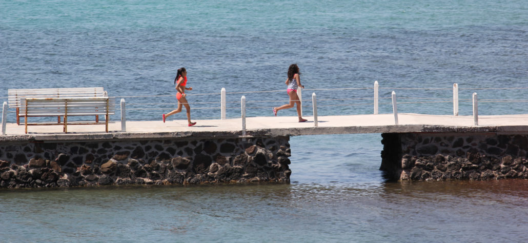 girls running on pier in Mexico