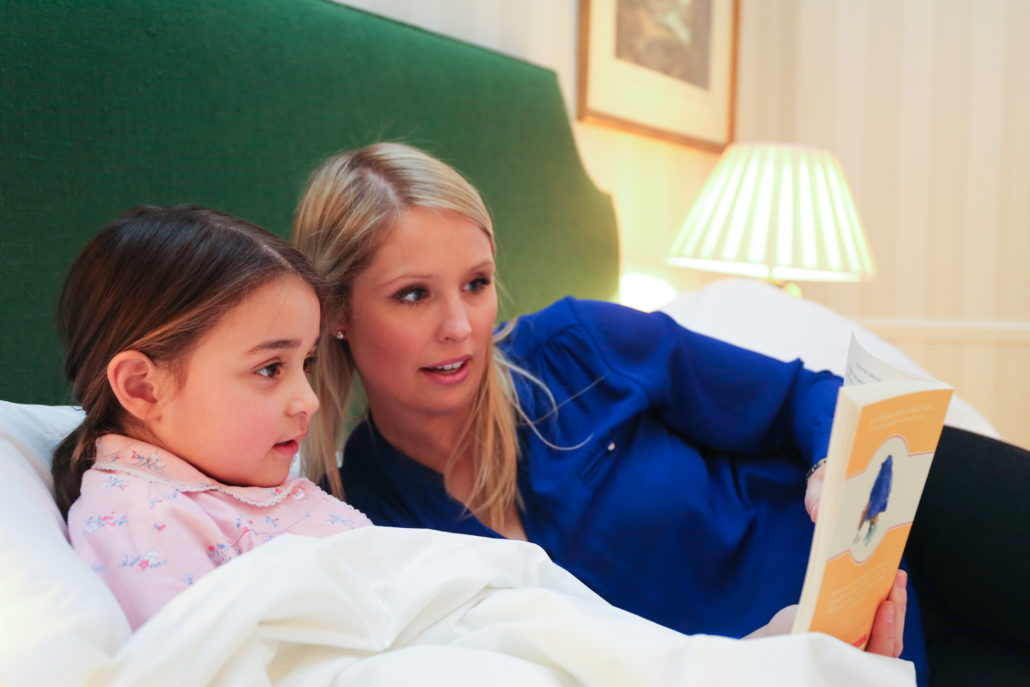 Mother and daughter reading Paddington Bear in the hotel room