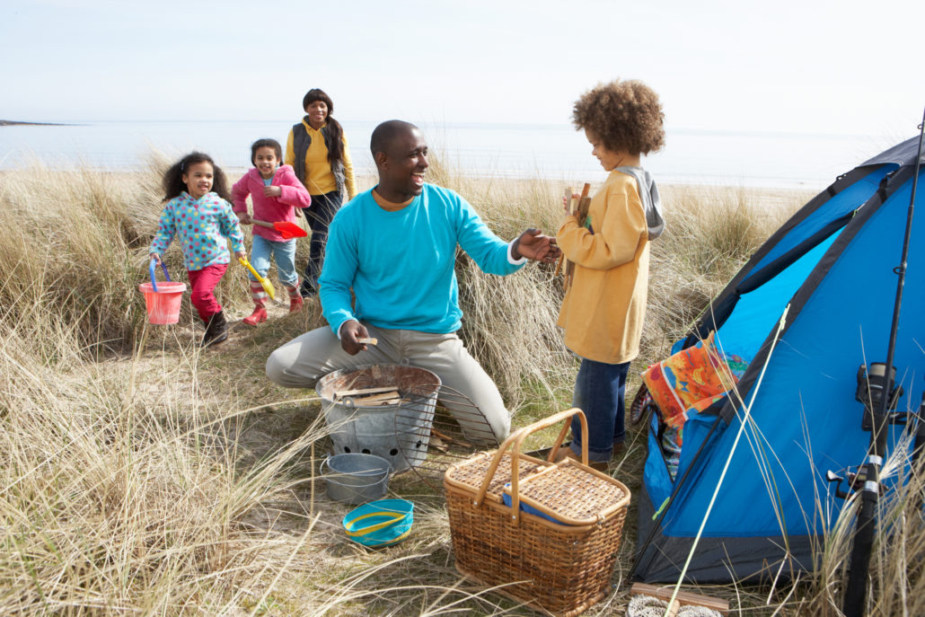family camping on beach with picnic