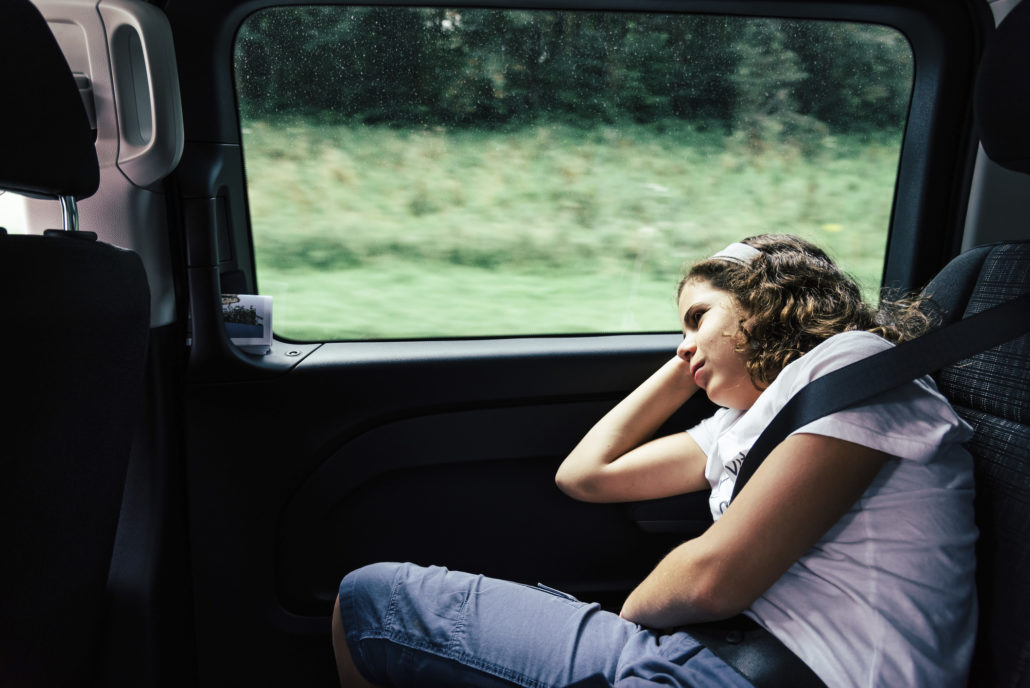 sleeping in the backseat of a car on a trip