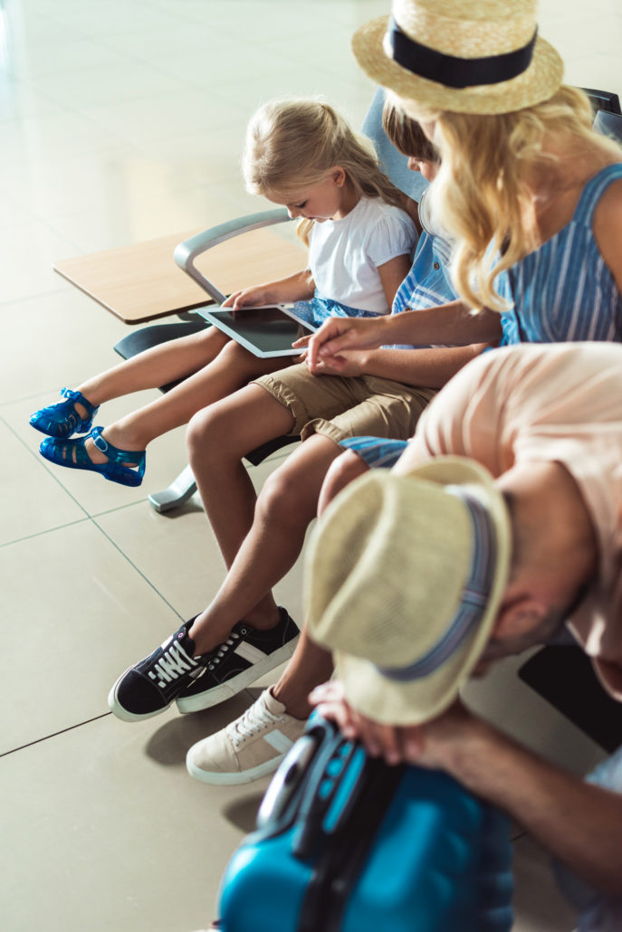 Kids using tablet at airport