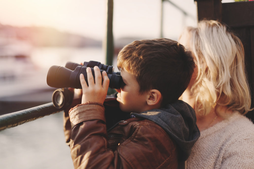 Little boy watching into distantance by binoculars with mother