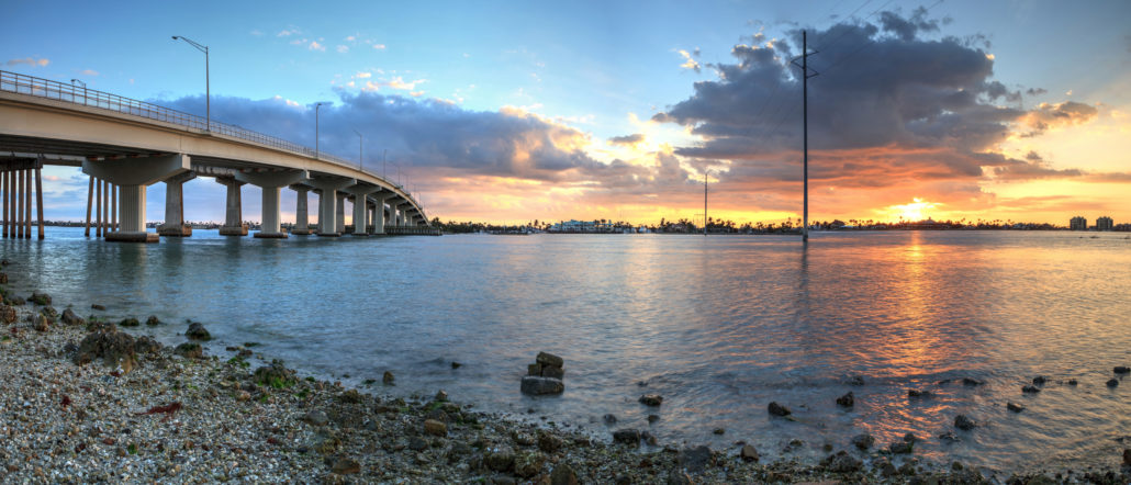 Sunset over the bridge roadway that journeys onto Marco Island,. Coastline, water.