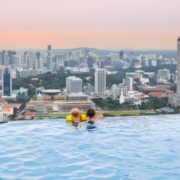 Kids swim in Singapore roof top swimming pool. Downtown, high.
