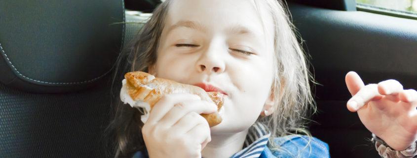 girl sitting inside car eating