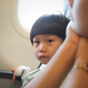 Little boy sitting at window seat in airplane