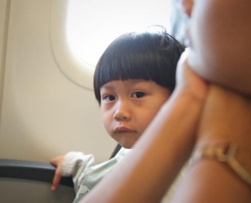 Little boy sitting at window seat in airplane
