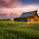 Early morning sunshine illuminating the iconic Moulton barn and Teton peaks in Grand Teton National Park, WY