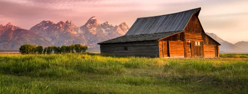 Early morning sunshine illuminating the iconic Moulton barn and Teton peaks in Grand Teton National Park, WY