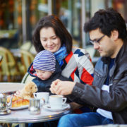 family of three in Parisian outdoor cafe