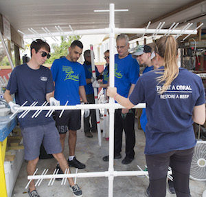 "Tourism Cares volunteers work with Coral Restoration Foundation staffers Friday, May 11, 2018, in Key Largo, Florida, to build coral ""trees,"" each to serve as underwater foundations for up to 60 baby corals. From left in front are Dan Burdeno, CRF; Vinicius Soares and Jose Menchero, both of Navigation Aviation & Tourism Management; Jes Stulc of Carlson Wagonlit; Lisa Sanchez of Carnival Foundation; and Callie Stephenson of CRF."