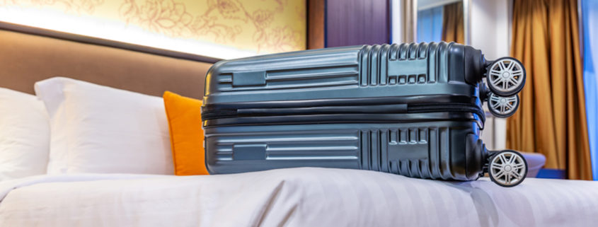 Modern small luggage on bed in small hotel room © Somdul | Dreamstime.com