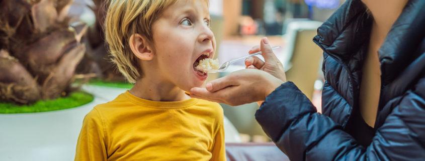 Young boy eating food while waiting for his flight © Elizaveta Galitskaya | Dreamstime.com