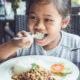 Kid eating in a restaurant © Phanuwatn   Dreamstime.com