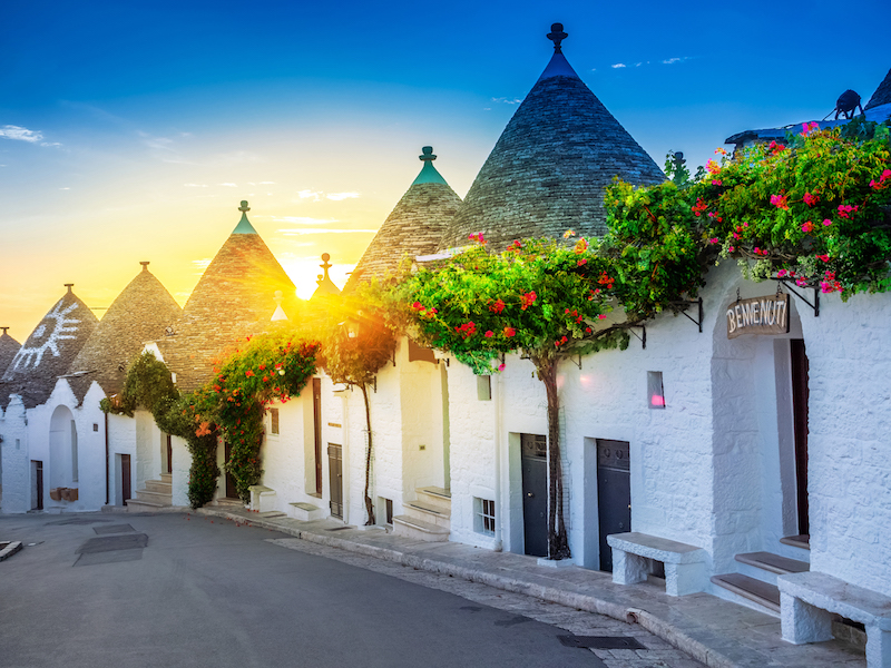 Traditional Trulli houses in Alberobello village, illuminated by sunrise. Apulia region - Italy.