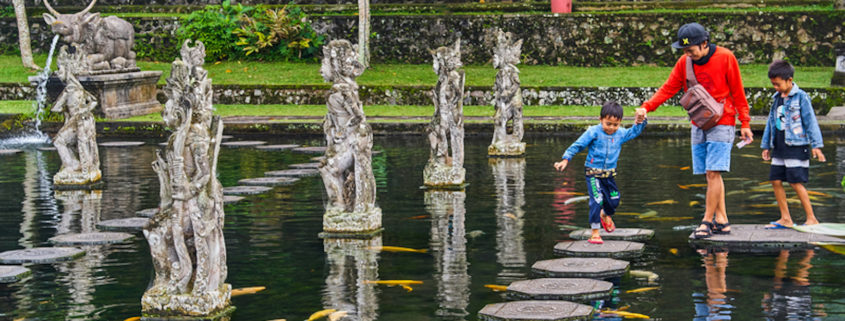 Family at Tirta Gangga water palace in Bali © Alexey Pelikh | Dreamstime.com