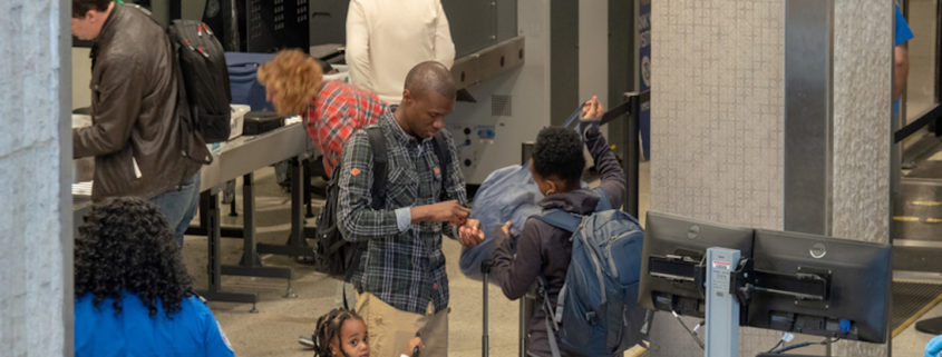 Family gathering belongings after passing through a Transportation Security Administration (TSA) checkpoint at JFK Airport © David Tran - Dreamstime.com