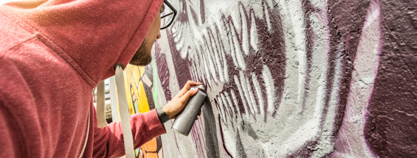 Street artist painting colorful graffiti.
