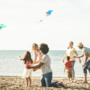 Families playing with kite at beach vacation. Photo: Mirko Vitali - Dreamstime.com