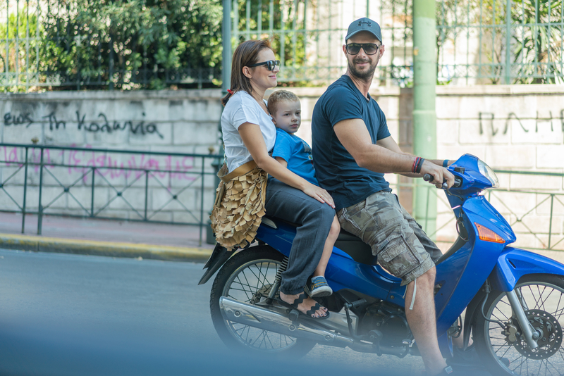 Family traveling on motorbike in Athens, Greece. Photo: Saloni1986 | Dreamstime.com