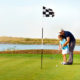 Young father teaching daughter to play golf on putting on green. Photo: Darya Petrenko | Dreamstime.com