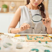 Jewelry designer looking at her work with magnifying glass.