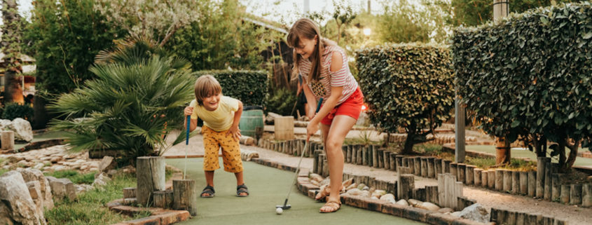 Kids playing mini golf.