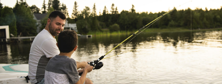 A Dad and son fishing on lake.