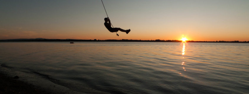 Rope swing over Lake Champlain in Vermont.
