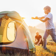Father and son setting camping tent on the sunset mountain valley